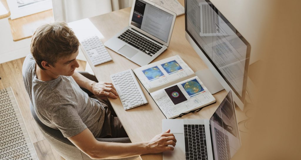 Man using 3 computers